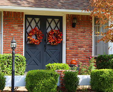 Tulalip Housing and Construction - Privacy Policy landing page image of a brick home with two fall colored wreaths on front of the double doors.