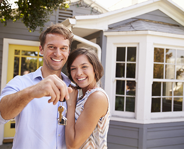 Tulalip Housing and Construction - Tenant Services Department Resources landing page image of a couple, standing in front of their new home, holding up theirs very happy.